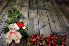 Le nounours de Noël concernent le fond en bois Photographie stock libre de droits