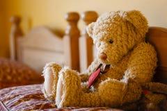 Le nounours triste concernent un lit Photo libre de droits