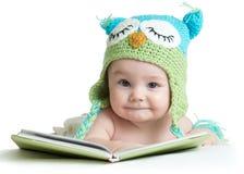 Le nourrisson de bébé dans le hibou drôle a tricoté le hibou de chapeau avec le livre sur le fond blanc Photo stock