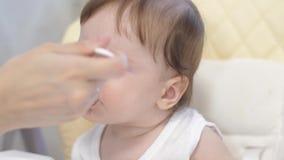 Le nourrisson mange de l'aliment pour bébé avec plaisir banque de vidéos
