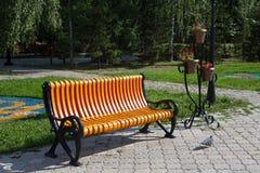 Le nouveau banc orange en parc de ville du nom russe de ville de Petropavl est Petropavlovsk Photographie stock libre de droits
