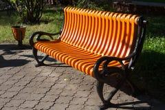 Le nouveau banc orange en parc de ville du nom russe de ville de Petropavl est Petropavlovsk Photos stock