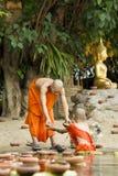 Le novice préparent les bougies de flottement dedans au Bouddha. Image libre de droits