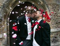 Le nozze gay, sposi lasciano la chiesa del villaggio dopo il matrimonio ai sorrisi ed ai coriandoli fotografia stock