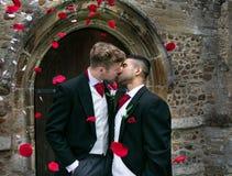 Le nozze gay, sposi lasciano la chiesa del villaggio dopo il matrimonio ai sorrisi ed ai coriandoli immagine stock libera da diritti