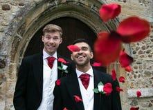 Le nozze gay, sposi lasciano la chiesa del villaggio dopo il matrimonio ai sorrisi ed ai coriandoli fotografia stock libera da diritti