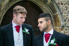 Le nozze gay, sposi lasciano la chiesa del villaggio dopo il matrimonio con i sorrisi e tenersi per mano grandi fotografia stock libera da diritti