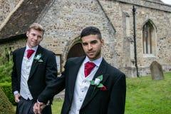 Le nozze gay, sposi lasciano la chiesa del villaggio dopo il matrimonio con i sorrisi e tenersi per mano grandi fotografia stock