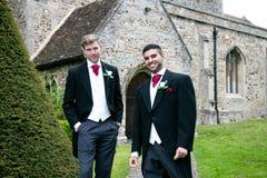 Le nozze gay, sposi lasciano la chiesa del villaggio dopo il matrimonio con i sorrisi e tenersi per mano grandi fotografie stock libere da diritti