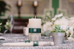 Le nozze hanno decorato le candele con la fibula d'argento ed i nastri verdi accanto al vaso d'argento Fotografie Stock