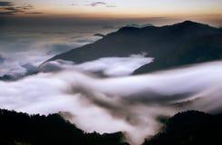 le nubi gradicono la cascata Immagini Stock