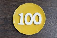 Le numéro cent du plat jaune Image libre de droits