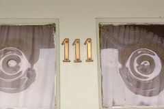 Le numéro de maison 111 se connectent la porte peinte verte Photos libres de droits