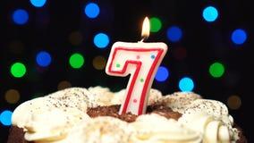 Le numéro 7 sur le gâteau - burning de bougie de sept anniversaires - soufflez à l'extrémité Fond brouillé par couleur banque de vidéos
