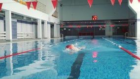 Le nuotate del cappuccio dell'uomo in rosso nello stagno 4K archivi video