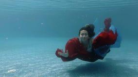 Le nuotate ed i giochi dell'adolescente con un panno rosso e blu subacqueo al fondo dello stagno stock footage