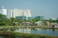 Le nuove costruzioni di appartamento torreggiano le case impoverite fuori di Saigon nel Vietnam Immagini Stock
