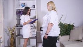 Le nutritionniste mesure une taille du client et note des indicateurs dans un carnet photo libre de droits