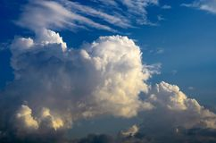 Le nuvole bianche enormi che si muovono attraverso il cielo blu sono illuminate dal sole al tramonto Fotografia Stock Libera da Diritti
