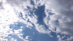 Le nuvole bianche scompaiono nel sole caldo su cielo blu Il moto al rallentatore si appanna il fondo del cielo blu stock footage