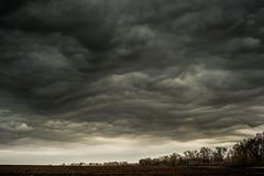 Le nuvole blu galleggiano lentamente attraverso il cielo, sopra il campo recentemente arato, mattina in anticipo della molla immagine stock
