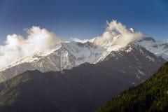 Le nuvole commoventi ad alta neve alzano il plateau verticalmente della montagna Immagine Stock