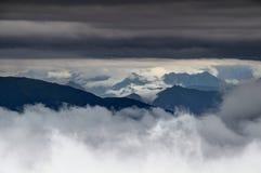 Le nuvole d'attaccatura basse turbinano intorno alle creste delle alpi di Carnic, Italia Fotografia Stock Libera da Diritti