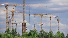 Le nuvole dell'estate e il construcrion multiplo cranes il lasso di tempo del teleobiettivo 4K stock footage