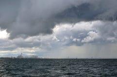 Le nuvole di pioggia grige pesanti accadono nella città vicino al mare Immagini Stock