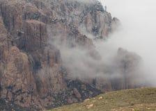Le nuvole di spostamento parzialmente celano il fronte della montagna fotografie stock