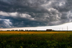 Le nuvole di tempesta sono avvicinantesi ed appendenti sopra il cottage solo Fotografie Stock Libere da Diritti