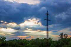 Le nuvole drammatiche scure della torre ad alta tensione espongono al sole i raggi del ` s Immagine Stock Libera da Diritti