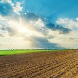 Le nuvole ed il tramonto sopra l'agricoltura sistemano in primavera Fotografia Stock