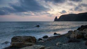 Le nuvole galleggiano sopra la costa di mare al tramonto archivi video