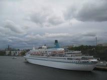 Le nuvole scure sono nave di lusso dell'incrociatore della copertura in porto fotografia stock