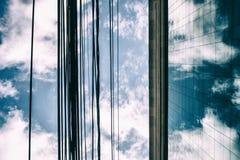 Le nuvole in un cielo blu hanno riflesso in finestre di vetro di un edificio per uffici Immagine Stock