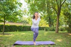 Le och den fantastiska kvinnan är praktiserande yoga i det gröna gräset En dam är snygg, och göra sportar öva i parkera Fotografering för Bildbyråer