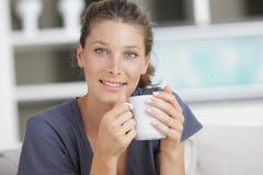 Le och dricka kaffe för ung kvinna royaltyfria bilder