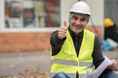 Le och lyckad väg-och vattenbyggnadsingenjör som visar det ok tecknet Arkivfoto