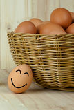 Le och lyckligt ägg mot hinken av ägg arkivbilder
