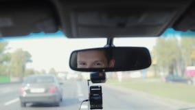 Le och talande man i en spegel, medan köra bilen på en upptagen väg i en stad Stiligt mans framsidan Lopp med bilen arkivfilmer