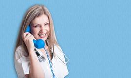 Le och vänlig medicinsk doktor med telefonen arkivfoton