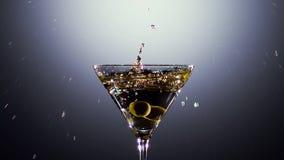 Le olive fresche verdi cadono in vetro con il cocktail Movimento lento stock footage