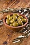 Le olive verdi in una ciotola ceramica hanno sistemato con le foglie Fotografia Stock Libera da Diritti