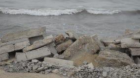Le onde del mare si schiantano contro la roccia, le onde del mar Caspio stanno cadendo su una costruzione metallica rocciosa e ve stock footage