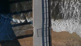 Le onde dell'estate si rompono su una spiaggia e su un pilastro caldi della California video d archivio