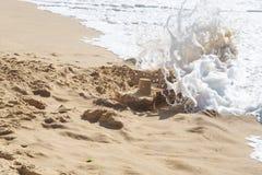Le onde dell'oceano distruggono il castello della sabbia del bambino Fotografia Stock Libera da Diritti