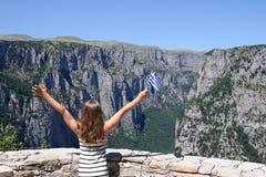 Le onde della bambina con una bandiera greca su Vikos si rimpinzano di Zagoria Fotografie Stock Libere da Diritti