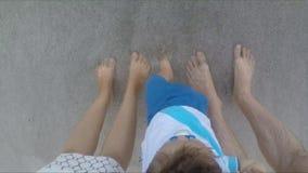Le onde di oceano che lavano sopra i piedi famiglia, mamma, papà ed il figlio, la famiglia passa un buon tempo sulla spiaggia stock footage