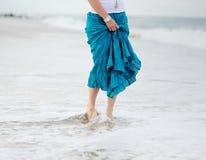 Le onde di oceano lavano i piedi della giovane donna Fotografia Stock Libera da Diritti